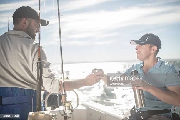 Two men having a coffee break on boat with fishing rods