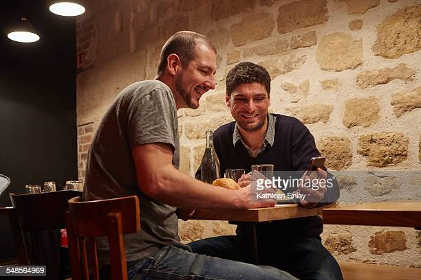 Two men having lunch in restaurant, one man showing the other his smartphone screen