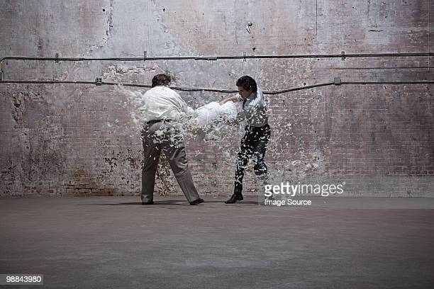 Two men having pillow fight in warehouse