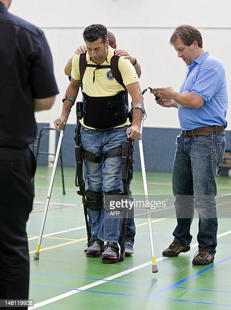 Two men help Dutch DJ and television presenter Marc de Hond as he tests his exoskeleton in a rehabilitation center in Amsterdam on July 10 2012 The...