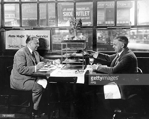 Two men helping themselves to a meal from the Auto Magic Table Service system in the restaurant at Hotel Warren Massachusetts circa 1936 The diners...