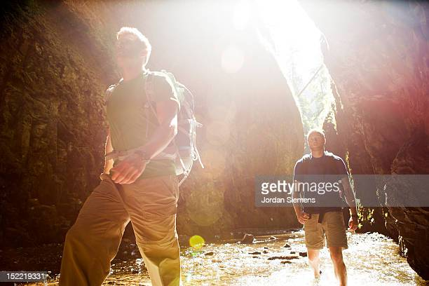 Two men hiking a narrow canyon.