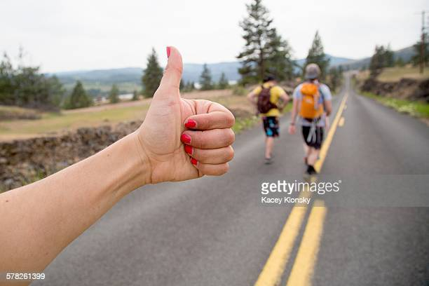 Two men hiking along road, while woman thumbs a lift, focus on hand