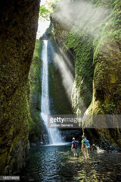 two men hiking to a waterfall. - columbia river gorge stock pictures, royalty-free photos & images