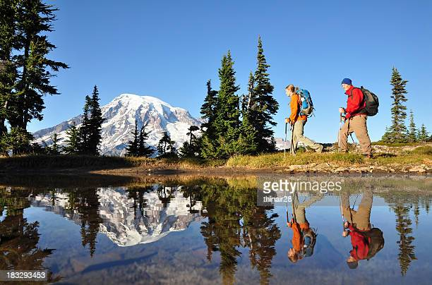 two men hiking with mt. rainier in the background - washington state stock pictures, royalty-free photos & images