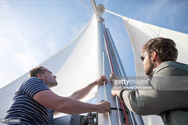 Two men hoisting sail on yacht