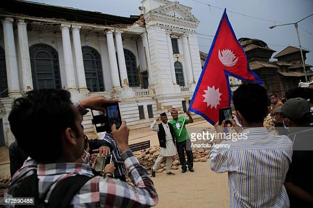 Two men hold a flag of Nepal as they pose for a picture in front the debris of buildings in Kathmandu on May 8 after the devastating 78magnitude...