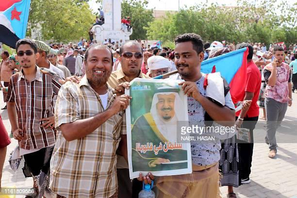 Two men hold a portrait of Saudi Arabia's King Salman bin Abdulaziz as Yemeni Southern separatists supporters wave flags of the former South Yemen...