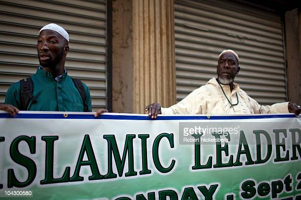 Two men hold a sign as leaders from various Muslim organizations hold a press conference in front of the proposed site of the Park51 Mosque near...