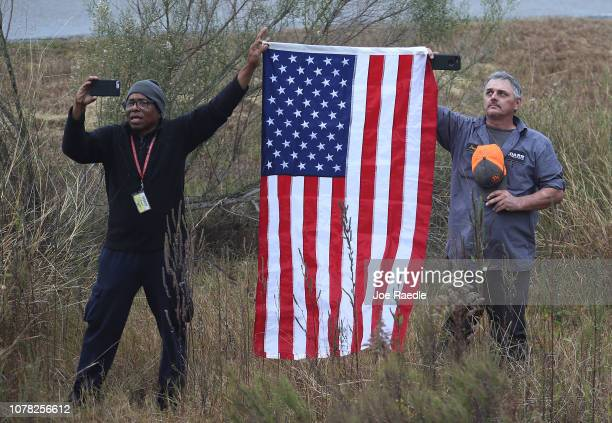 Two men hold a US flag as the train carrying former President George HW Bush to his final resting place passes by on December 6 2018 in Texas...