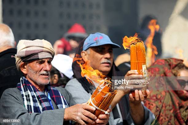 """Two men hold candles lit from the """"Holy Fire"""" which comes from Jerusalem in the West Bank city of Bethlehem. On Saturday, dubbed by Eastern Orthodox..."""