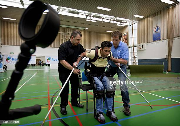 Two men hold Dutch DJ and television presenter Marc de Hond as he tests his exoskeleton in a rehabilitation center in Amsterdam on July 10 2012 The...