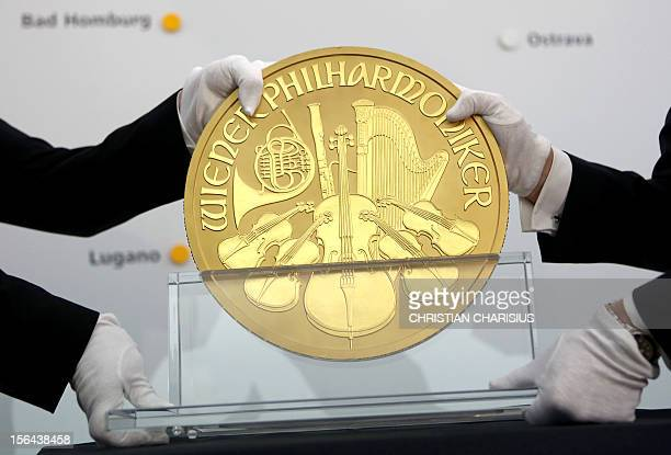 Two men hold Europe's biggest gold coin during an exhibition at the Pro Aurum trade house in Hamburg northern Germany on November 15 2012 The...