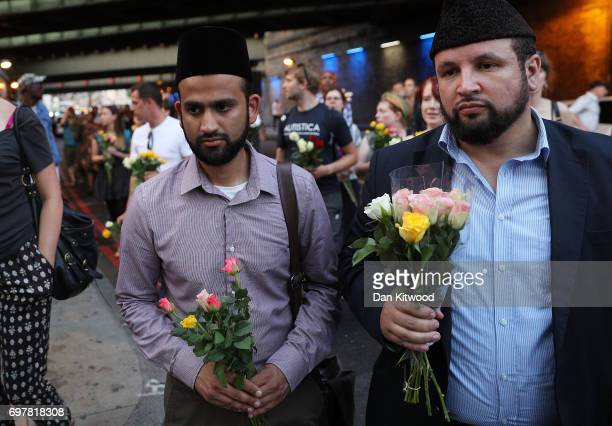 Two men hold flowers as they attend a vigil outside Finsbury Park Mosque on June 19 2017 in London England Worshippers were struck by a hired van as...