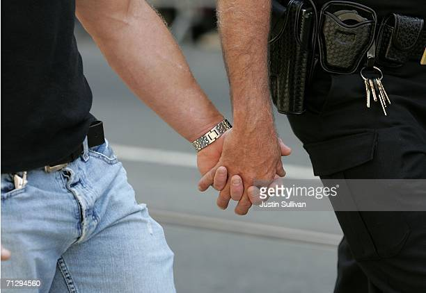 Two men hold hands as they participate in the 36th annual LGBT Pride Parade June 25, 2006 in San Francisco. Hundreds of thousands of spectators lined...