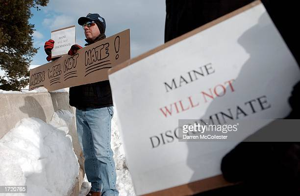 Two men hold peace signs while protesting at a NeoNazi rally held by supporters of the World Church of the Creator January 11 2002 in Lewiston Maine...