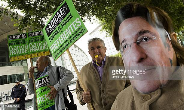 Two men hold placards and one wears a mask of Spanish bank Bankia president Jose Ignacio Goirigolzarri as they protest against fraud outside the...