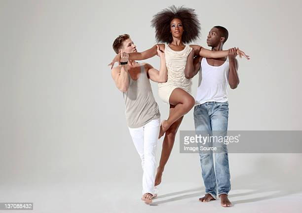 Two men holding a young woman off the ground