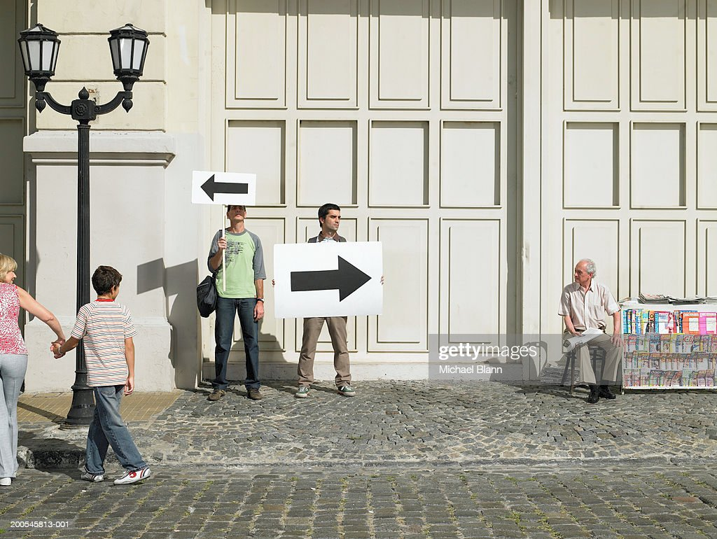 Two men holding arrow placards pointing in different directions : Stock Photo