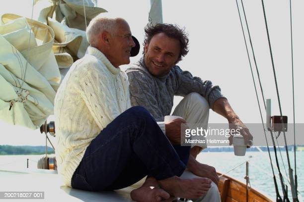 Two men holding coffee cups sitting on yacht, smiling