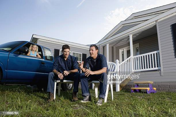 Two men holding cold drinks sitting on lawn chairs in front of trailer home