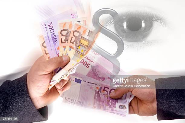 two men holding euro note, eye watching, curruption - money laundering stock photos and pictures