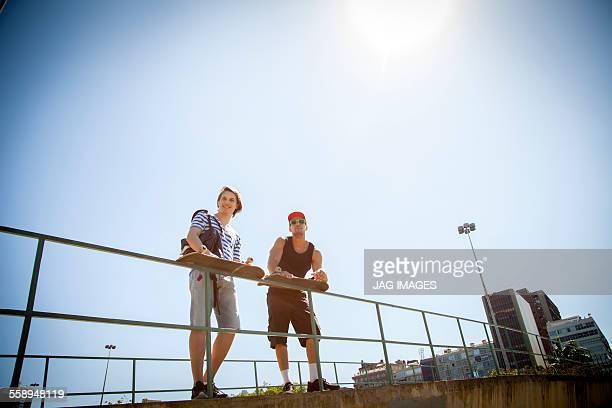 two men, holding skateboards, leaning on railings, low angle view - vedação de corrimão imagens e fotografias de stock