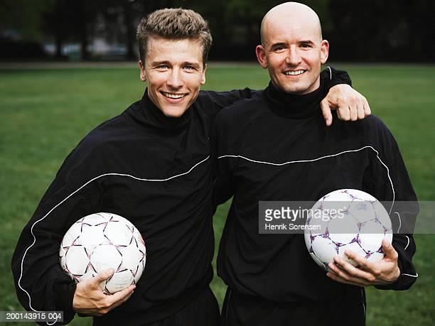 Two men holding soccer balls, wearing sport uniform, smiling, portrait