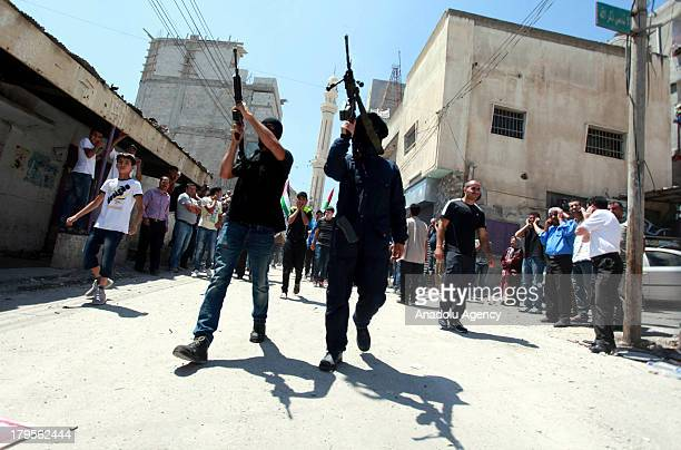 Two men holding their rifles in front of the funeral march at the funeral of three Palestinians on August 262013 at the Qalandia Refugee Camp near...