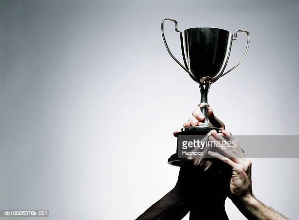 two men holding trophy, close-up - récompense photos et images de collection