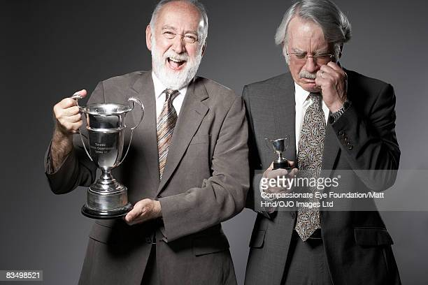 Two men holding very different sized trophies