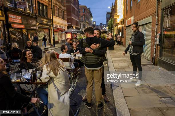 Two men hug as bars on Thomas Street in the Northern Quarter set out tables for customers on the closed road on July 04 2020 in Manchester England...