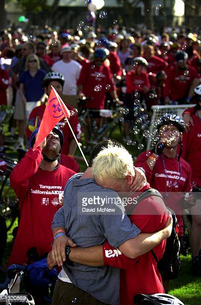 Two men hug as they remember those who have died of AIDS during the closing ceremonies of the California eighth annual AIDSRide June 9 2001 in Los...