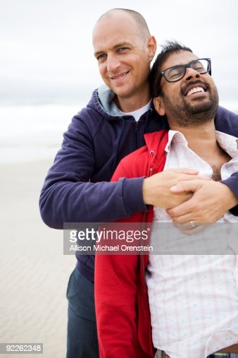 two men hugging on the beach