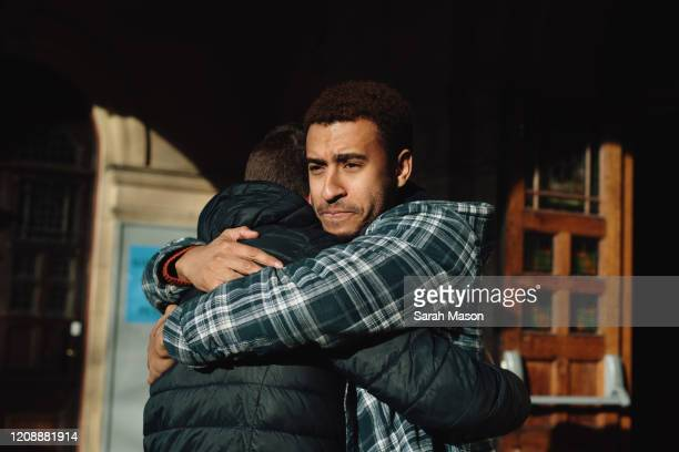 two men hugging - touching stock pictures, royalty-free photos & images
