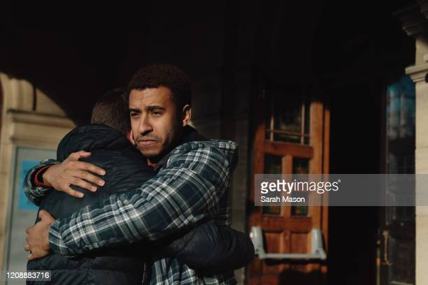 two men hugging - masculinity stock pictures, royalty-free photos & images