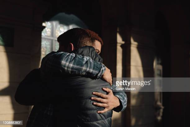 two men hugging - prop stock pictures, royalty-free photos & images