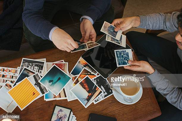 Two men in a cafe looking at photo prints