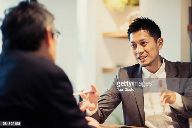 two men in a casual meeting in a cafe - japanischer abstammung stock-fotos und bilder