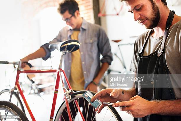 Two men in a cycle repair shop, one holding a smart phone and credit card. Paying by contactless card.