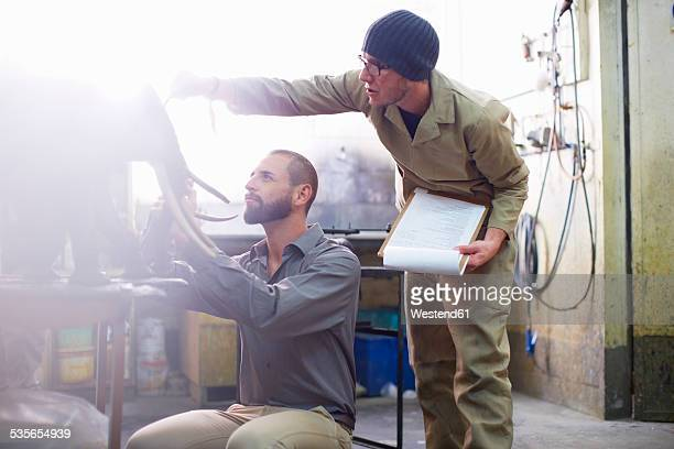 Two men in a sculptors workshop looking at elephant statue