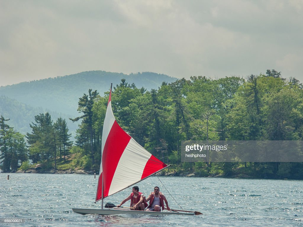 Two men in a small sailboat on Lake George, New York, USA : Stock Photo