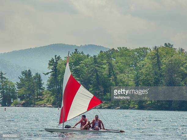 Two men in a small sailboat on Lake George, New York, USA