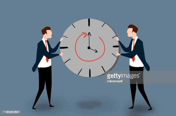 two men in a suit holding a clock - clocks go forward stock pictures, royalty-free photos & images