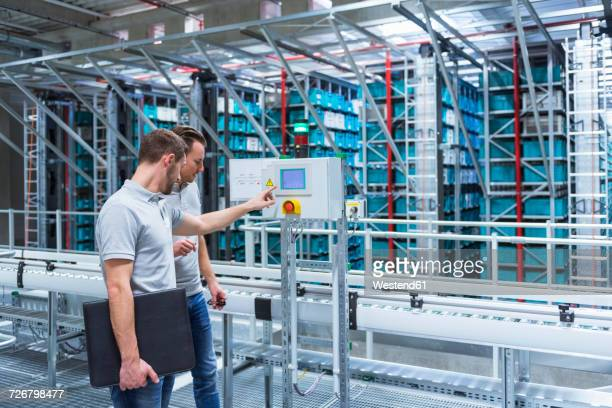 Two men in automatized high rack warehouse