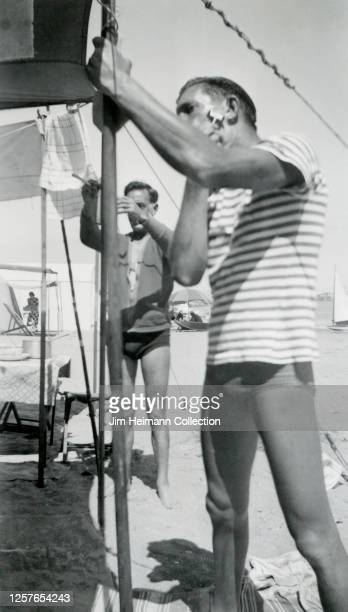 Two men in bathing suits shave their faces beneath an awning during a beach camping trip, circa 1938.