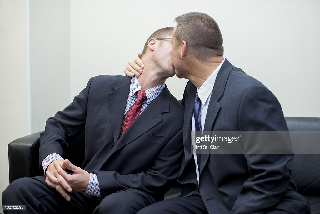 Gay men in suits kissing
