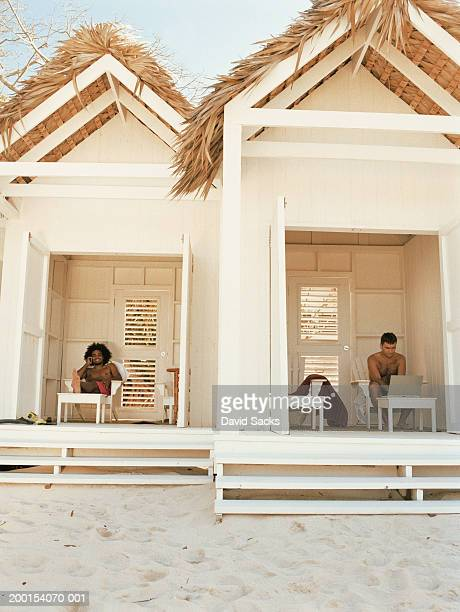 Two men in cabana, one man using mobile phone, other man using laptop