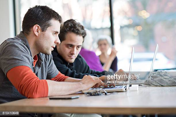 Two men in cafe work on laptop