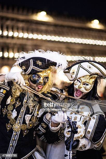 Two men in cat's masks dressed as musketeer musicians posing at Saint Mark's Square on February 27, 2014 in Venice, Italy. The 2014 Carnival of...